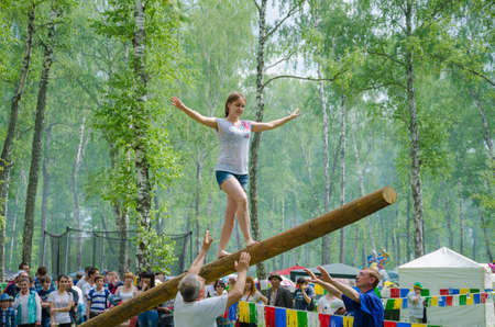 field work: Kazan, Republic of Tatarstan, Russia - May 28, 2016: The young girl balancing goes on a swinging long log. Sabantuy (translated from Tatar - feast of the plow) is a traditional celebration of the end of spring field work.