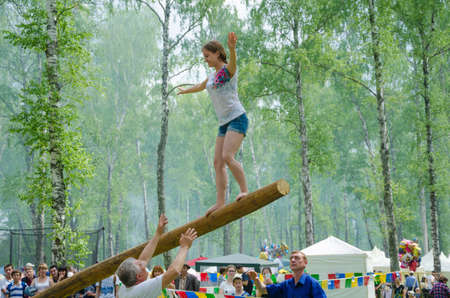 shoeless: Kazan, Republic of Tatarstan, Russia - May 28, 2016: The young girl balancing goes on a swinging long log. Sabantuy (translated from Tatar - feast of the plow) is a traditional celebration of the end of spring field work.