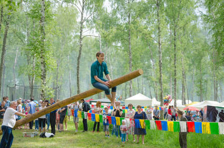 field work: Kazan, Republic of Tatarstan, Russia - May 28, 2016: The young man sitting on a log. Sabantuy (translated from Tatar - feast of the plow) is a traditional celebration of the end of spring field work.