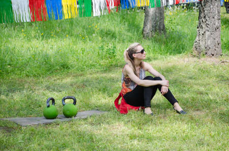 field work: Kazan, Republic of Tatarstan, Russia - May 28, 2016: The girl sitting next to the kettlebell. Sabantuy (translated from Tatar - feast of the plow) is a traditional celebration of the end of spring field work.