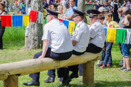 field work: Kazan, Republic of Tatarstan, Russia - May 28, 2016: Police officers have a rest sitting on a log and watch the competitions. Sabantuy (translated from Tatar - feast of the plow) is a traditional celebration of the end of spring field work.