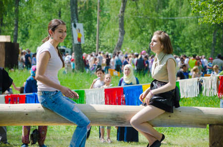 field work: Kazan, Republic of Tatarstan, Russia - May 28, 2016: Girls sit on a log and prepare for fight on bags. Sabantuy (translated from Tatar - feast of the plow) is a traditional celebration of the end of spring field work. Editorial