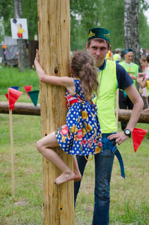 field work: Kazan, Republic of Tatarstan, Russia - May 28, 2016: Girl climbs on a wooden post. Sabantuy (translated from Tatar - feast of the plow) is a traditional celebration of the end of spring field work. Editorial