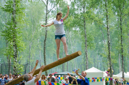 translated: Kazan, Republic of Tatarstan, Russia - May 28, 2016: The young girl balancing goes on a swinging long log. Sabantuy (translated from Tatar - feast of the plow) is a traditional celebration of the end of spring field work.