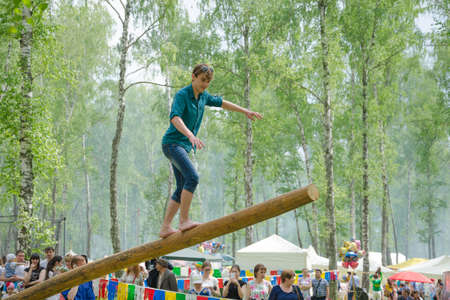 field work: Kazan, Republic of Tatarstan, Russia - May 28, 2016: The young man balancing goes on a swinging long log. Sabantuy (translated from Tatar - feast of the plow) is a traditional celebration of the end of spring field work.