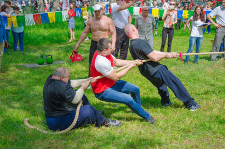 translated: Kazan, Republic of Tatarstan, Russia - May 28, 2016: Competitions in tug of war among men. Sabantuy (translated from Tatar - feast of the plow) is a traditional celebration of the end of spring field work.
