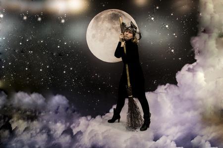 Una bruja en ropa de color negro con una escoba Foto de archivo
