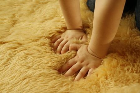 pamper: Hands of child on a fluffy carpet