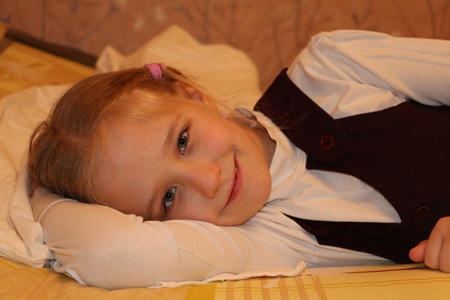 modesty: Pretty schoolgirl is lying on the bed