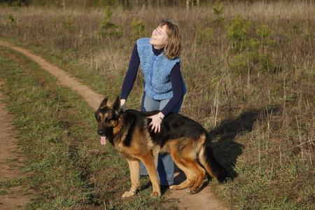 german girl: Girl and German shepherd dog on the field