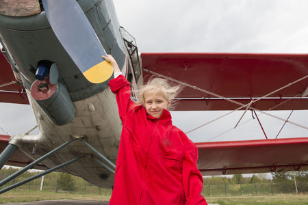 airfield: Girl and an old airplane on the airfield Stock Photo