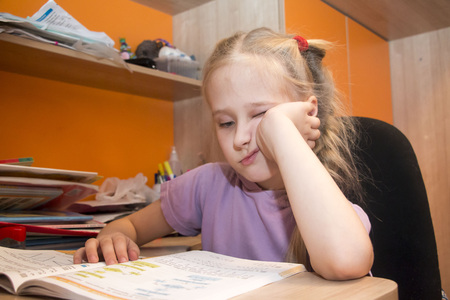 Young schoolgirl is sitting near the desk Stock Photo