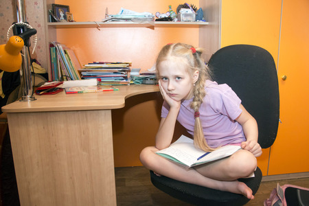 modesty: Young schoolgirl is sitting near the desk Stock Photo