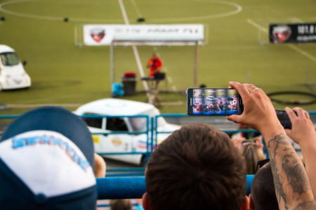 spectators: Russia, Kirov - August, 09, 2016: Spectators are taking pictures of extreme auto show in Kirov city in 2016 Editorial