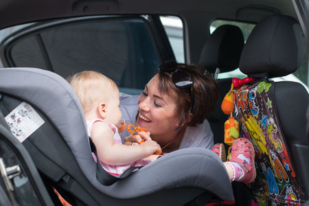 kin: Nice girl and small baby in the car Stock Photo