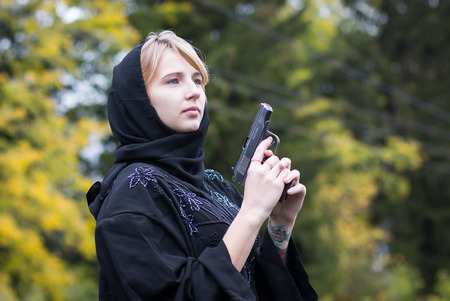 saboteur: Girl in muslim dress with arms in autumn day
