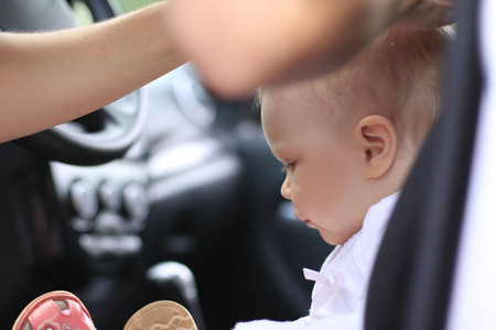 Sad baby in the car and the womans hands are making the hair style