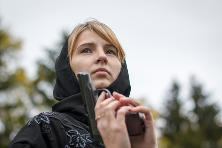Woman in muslim dress with arms in autumn day Stock Photo