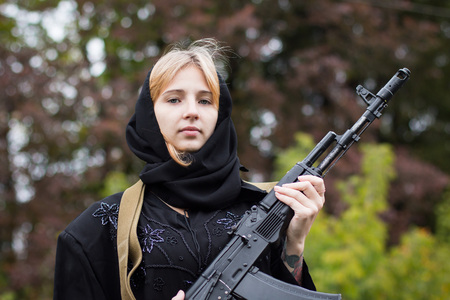 saboteur: Woman in muslim dress with arms in autumn day Stock Photo