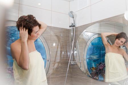 cabello corto: La muchacha bonita con el pelo corto en un precioso cuarto de baño Foto de archivo