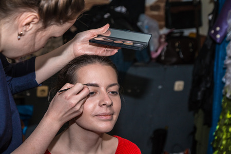 Make-up artist doing the make-up for beautiful girl Stock Photo