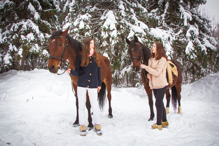 Twin sisters and horse in a white winter forest