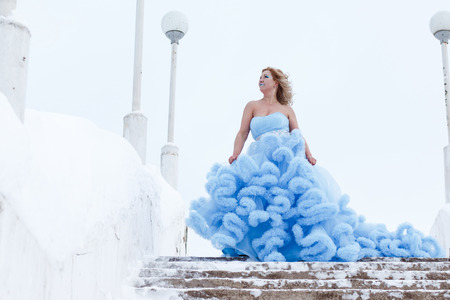 Woman in a beautiful blue dress in a winter day