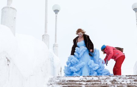 Preparation for shooting of woman in blue dress in the park in a winter day Stock Photo