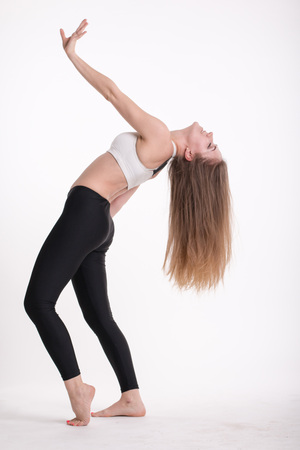 Slim sporty girl with long blond hair on white background Stock Photo