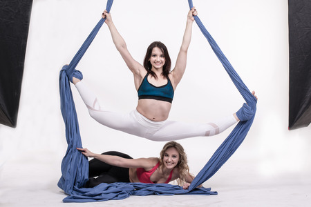 contortion: Nice girls and sports exercises with aerial silk Stock Photo