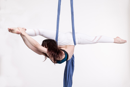 contortion: Nice girl and sports exercises with aerial silk Stock Photo