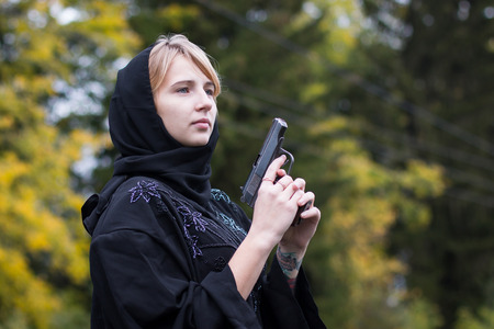 Muslim woman with arms in autumn day