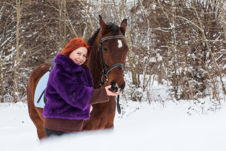 village man: Woman with red hair and big horse outdoor in winter day