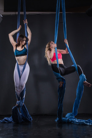 tissues: Nice girls and sports exercises with aerial silk Stock Photo