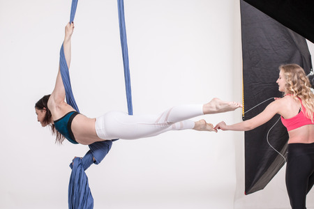 sexy girl dance: Nice girls and help in sports exercises with aerial silk Stock Photo