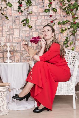 Ugly domineering woman is posing in red dress in studio