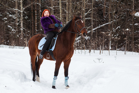 Woman with red hair and big horse outdoor in winter day