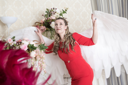 Ugly woman in a red dress with white angel wings posing in the Studio