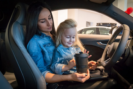 Klein meisje en moeder in tentoonstellingszaal voor auto Stockfoto