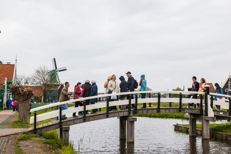 provinces: Netherlands, Zaanse Schans - April, 24, 2017: Windmill and the landscape around in a cloudy day in Zaanse Schans in 2017