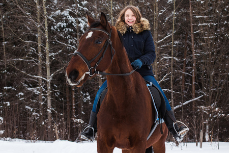 Girl teenager and big horse in a winter day