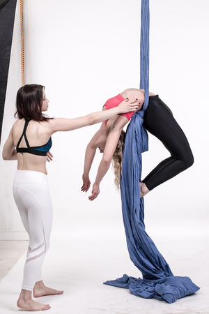 tissues: Nice girls and help in sports exercises with aerial silk Stock Photo