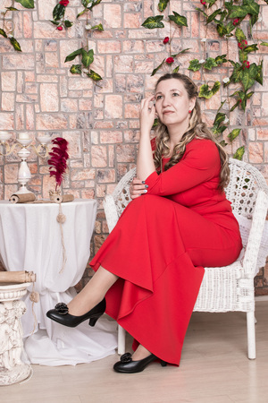 Ugly domineering woman is posing in red dress in studio