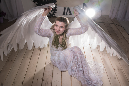 Ugly woman in a white dress with white wings is trying to look as angel