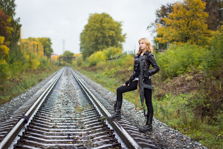 Girl with arms on the rails in autumn day