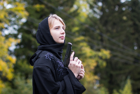 Girl with blond hair in black muslim dress with arms
