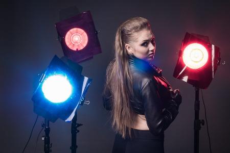 Meisje in een leren jas op het podium en drie gekleurde schijnwerpers Stockfoto - 81237251