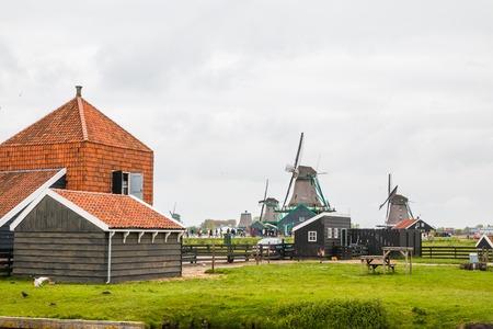 Netherlands, Zaanse Schans - April, 24, 2017: Windmill and the landscape around in a cloudy day in Zaanse Schans in 2017