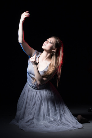 Actress in a grey dress on a dark stage during a rehearsal 版權商用圖片 - 81571393