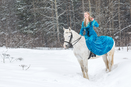 Woman in national dress and white horse in a forest in a winter day Zdjęcie Seryjne